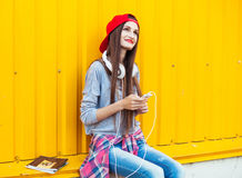 La chica joven escucha la música en los auriculares blancos Imagenes de archivo