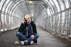 La chica joven escucha la música en auriculares grandes en el subterráneo Fotografía de archivo libre de regalías