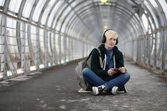 La chica joven escucha la música en auriculares grandes en el subterráneo Fotos de archivo libres de regalías
