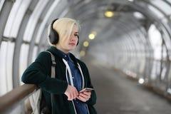 La chica joven escucha la música en auriculares grandes en el subterráneo Imagen de archivo