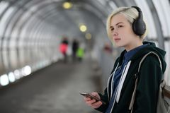 La chica joven escucha la música en auriculares grandes en el subterráneo Imagenes de archivo