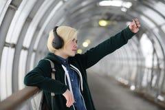 La chica joven escucha la música en auriculares grandes en el subterráneo Foto de archivo libre de regalías