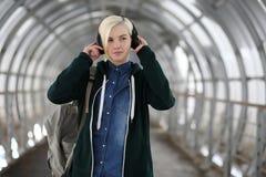 La chica joven escucha la música en auriculares grandes en el subterráneo Fotos de archivo