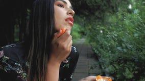 La chica joven española hermosa rompe desafiantemente el mandarín en su mano y lo muerde atractivo y mancha su cara 4K v?deo 4K almacen de video
