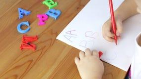 La chica joven está aprendiendo el alfabeto almacen de metraje de vídeo