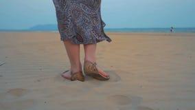 La chica joven está caminando a lo largo de la playa Tiró las piernas Cámara lenta almacen de video