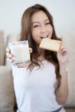 La chica joven está comiendo la tostada fresca que sostiene un vidrio de leche Imagenes de archivo