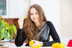 La chica joven está comiendo una naranja Foto de archivo libre de regalías