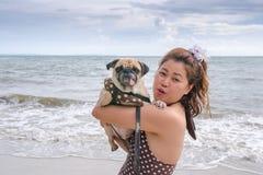 La chica joven está descansando con un perro en el mar fotografía de archivo