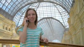 La chica joven está hablando en el teléfono móvil en alameda de compras metrajes
