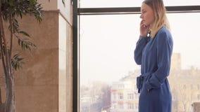 La chica joven está hablando en el teléfono móvil en alameda de compras almacen de metraje de vídeo