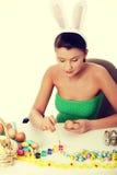 La chica joven está haciendo la decoración de pascua Fotografía de archivo libre de regalías