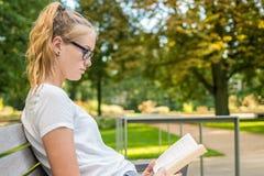 La chica joven está leyendo un libro en un banco fotografía de archivo libre de regalías