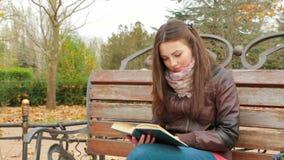 La chica joven está leyendo un libro en parque almacen de metraje de vídeo