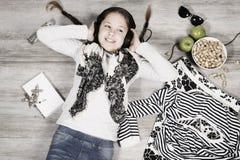 La chica joven está mintiendo en el piso y la música que escucha Fotografía de archivo libre de regalías