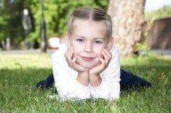 La chica joven está mintiendo en hierba verde y sonrisa Fotografía de archivo libre de regalías