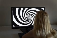 La chica joven está mirando espiral de la hipnosis en su ordenador Foto de archivo
