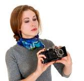 La chica joven está mirando la cámara del vintage Foto de archivo libre de regalías