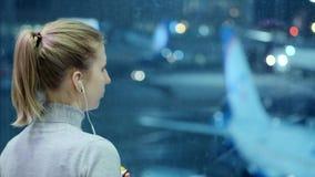 La chica joven está mirando un avión el aeropuerto Escucha la música a través de los auriculares Esperar mi vuelo almacen de video