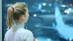 La chica joven está mirando un avión el aeropuerto Escucha la música a través de los auriculares Esperar mi vuelo almacen de metraje de vídeo
