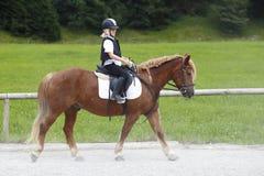 La chica joven está montando en un caballo Fotografía de archivo