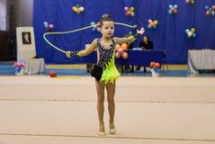 La chica joven está participando en una competencia de la gimnasia Fotos de archivo libres de regalías