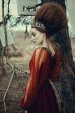 La chica joven está presentando en un vestido rojo con el peinado creativo fotos de archivo