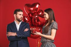 La chica joven está presentando un regalo y los globos a su hombre hermoso imagenes de archivo