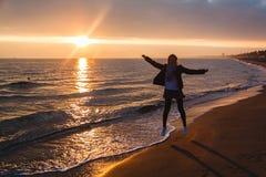 La chica joven está saltando por el mar durante puesta del sol en Terracina Foto de archivo libre de regalías