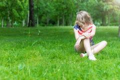 La chica joven está sonriendo y sentada feliz en la hierba en día soleado del verano Foto de archivo