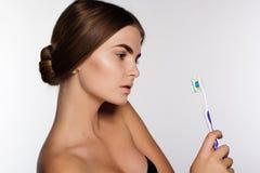 La chica joven está sosteniendo el cepillo de dientes Fotos de archivo libres de regalías