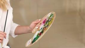 La chica joven está sosteniendo una paleta con las pinturas y dibuja una imagen, primer metrajes