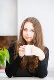 La chica joven está sosteniendo una taza Fotos de archivo