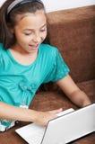 La chica joven está trabajando en la computadora portátil Fotografía de archivo