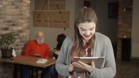 La chica joven está utilizando la tableta digital y está sonriendo a la cámara almacen de video