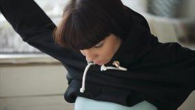 La chica joven está vistiendo un suéter negro acogedor, sentándose en un piso en un dormitorio almacen de metraje de vídeo