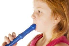 La chica joven está jugando en una flauta Fotos de archivo