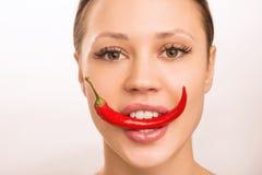 La chica joven está sosteniendo la pimienta roja con sus dientes Fotografía de archivo libre de regalías