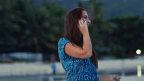 La chica joven feliz con el pelo largo en un vestido azul habla en el teléfono en la costa soleada entre las palmas y las montaña almacen de metraje de vídeo