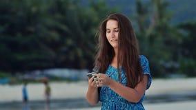 La chica joven feliz con el pelo largo en un vestido azul habla en el teléfono en la costa soleada entre las palmas y las montaña metrajes