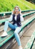 La chica joven feliz con sentarse de los auriculares escucha la música Fotos de archivo libres de regalías