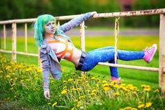 La chica joven feliz del retrato en festival del color del holi cuelga en una cerca vieja Imagenes de archivo