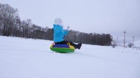 La chica joven feliz desliza abajo la diapositiva en nieve en un tubo inflable de la nieve y agita su mano Muchacha que juega en  almacen de video