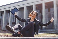 La chica joven feliz en negro es feliz con una nueva tableta que se sienta en la calle Imagen de archivo