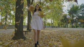 La chica joven feliz en la ropa blanca que camina en el parque que admira amarillo descendente del otoño se va y que disfruta de  almacen de video