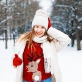 La chica joven feliz en un suéter rojo con un ciervo guiña y sonrisa Imágenes de archivo libres de regalías