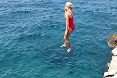 La chica joven feliz está saltando Foto de archivo libre de regalías
