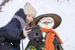 La chica joven feliz está tomando imágenes del selfie con un muñeco de nieve Fotografía de archivo