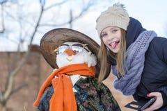 La chica joven feliz está tomando imágenes del selfie con un muñeco de nieve Imágenes de archivo libres de regalías