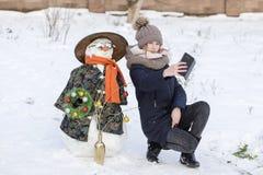 La chica joven feliz está tomando imágenes del selfie con un muñeco de nieve Foto de archivo